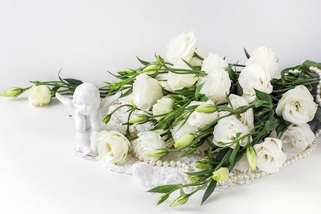 Flores brancas com pérolas e um anjo de cerâmica