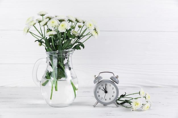Flores brancas de crisântemo em jarra de vidro perto do pequeno despertador na mesa de madeira