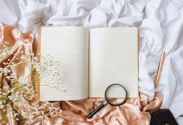 Flores brancas de gipsófila, caderno, caneta na cama. lençol branco e tecido de cetim dourado.