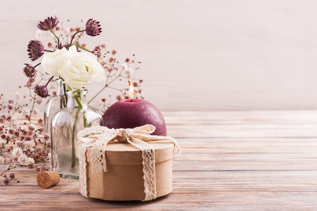 Flores brancas de ranúnculo e hortênsia com caixa de presente e vela