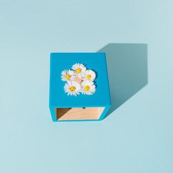 Flores brancas dispostas em um cubo azul. forma geométrica em um fundo azul. quadro criativo. conceito mínimo.