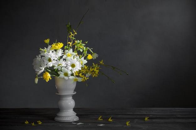 Flores brancas e amarelas da primavera na parede cinza do fundo