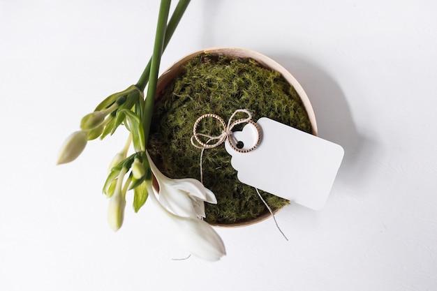 Flores brancas e anéis de casamento com tag em branco na tigela de musgo sobre fundo branco