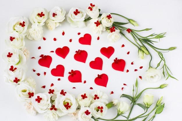 Flores brancas e flores vermelhas e corações de cetim vermelhos