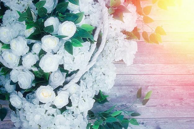 Flores brancas e folhas verdes em fundo de madeira. fundo de casamento