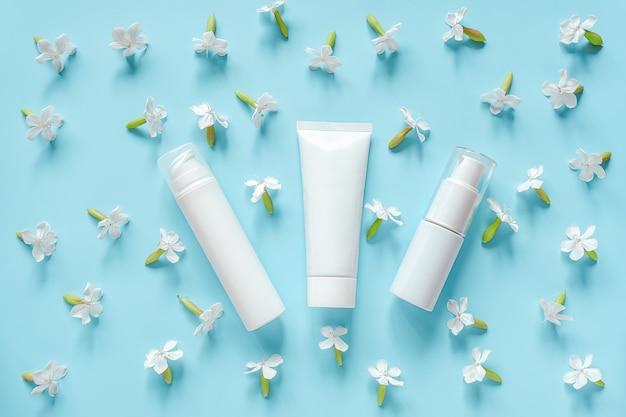 Flores brancas e três cosméticos tubo, garrafa de creme, pomada, creme dental. cosméticos orgânicos naturais