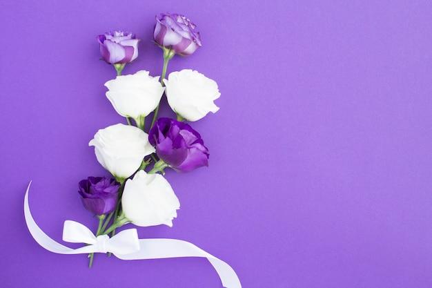 Flores brancas e violetas no fundo violeta com espaço de cópia