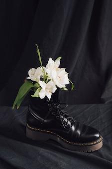 Flores brancas em bota de couro escura