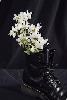 Flores brancas em bota escura