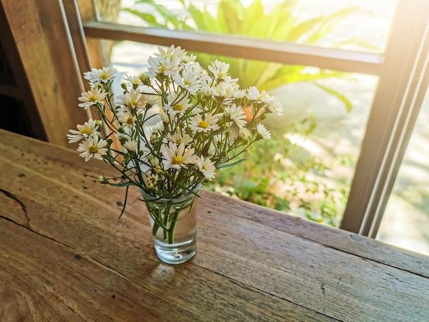 Flores brancas em panela de metal sobre a mesa de madeira