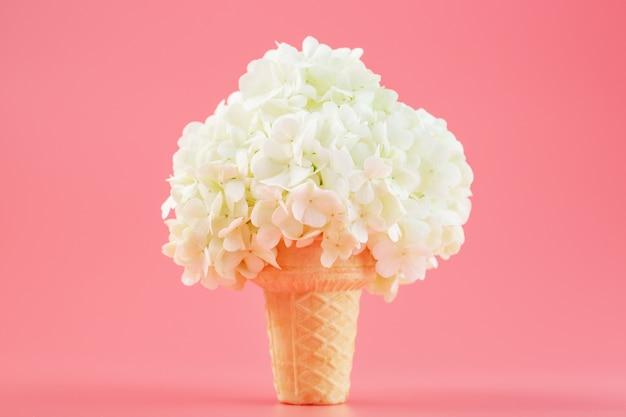 Flores brancas em um cone de waffle de sorvete em uma parede rosa.