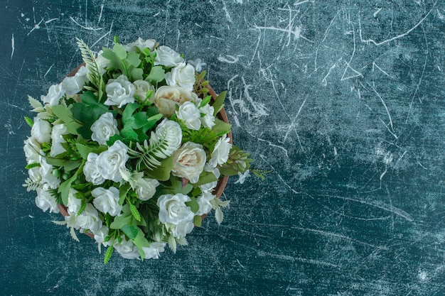 Flores brancas em uma placa de madeira, sobre o fundo azul.