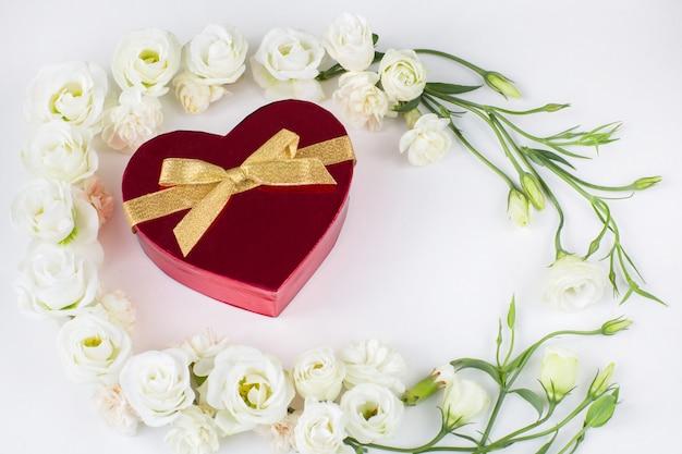 Flores brancas forradas com uma moldura e uma caixa vermelha em forma de coração