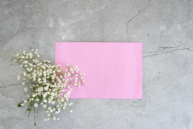 Flores brancas gypsophila com envelope rosa sobre fundo azul