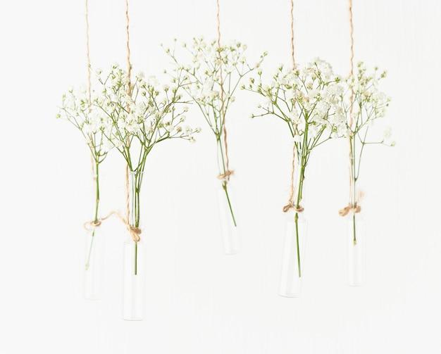 Flores brancas nos mini vasos de vidro que penduram no fundo branco. copie o espaço