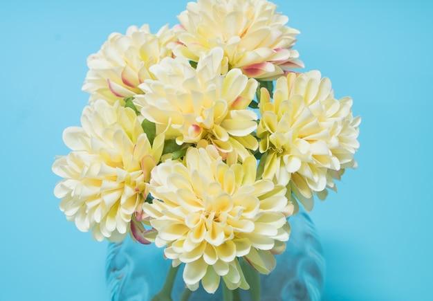 Flores brancas são dispostas em um vaso, colocado sobre uma mesa azul.