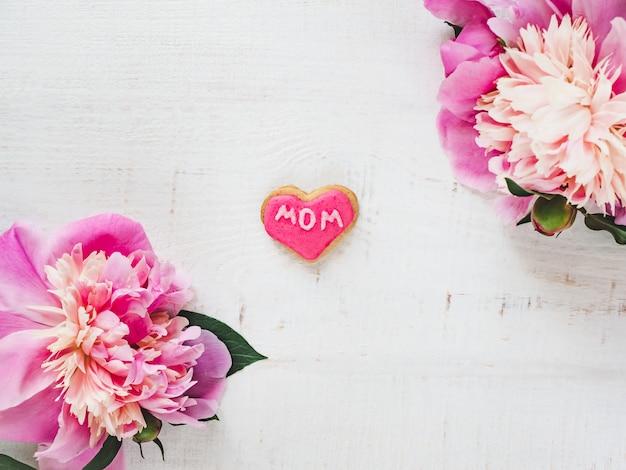 Flores brilhantes, biscoito rosa com a palavra mãe