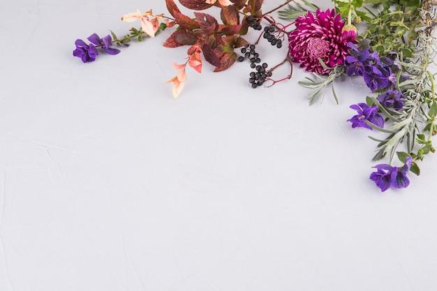 Flores brilhantes com ramos de plantas na mesa