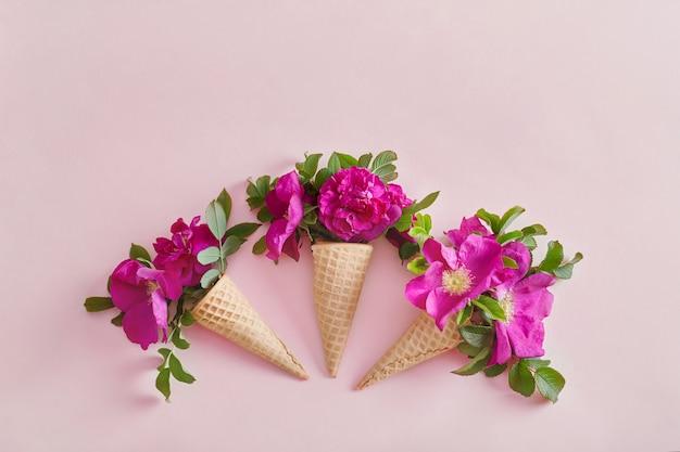 Flores brilhantes em um cone de waffle em uma superfície de papel rosa, flores da primavera, clima de verão. lugar para texto, cosméticos de flores de plantas diferentes