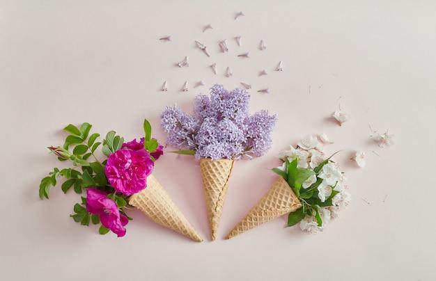 Flores brilhantes em um cone de waffle. flores da primavera, clima de verão. lugar para texto, cosméticos de flores de plantas diferentes