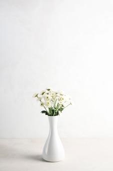 Flores claras em vaso na mesa