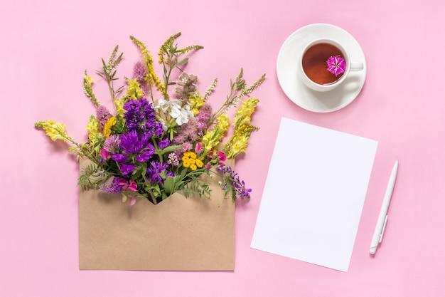 Flores coloridas de campo no envelope de ofício e xícara de chá de ervas vazio