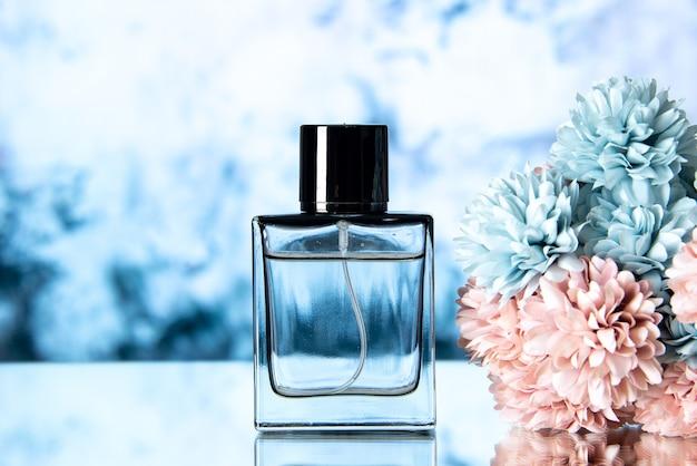 Flores coloridas de perfume elegante de vista frontal em fundo azul claro com espaço livre