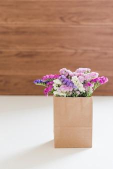 Flores coloridas decorativas em um saco de papel