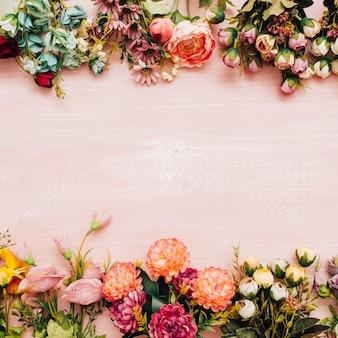 Flores coloridas em fundo rosa de madeira