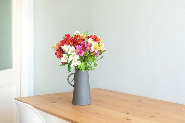 Flores coloridas em um vaso de cimento em uma mesa de madeira em uma sala cinza com copyspace