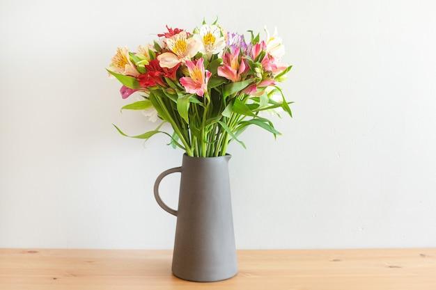 Flores coloridas em um vaso de cimento sobre uma mesa de madeira