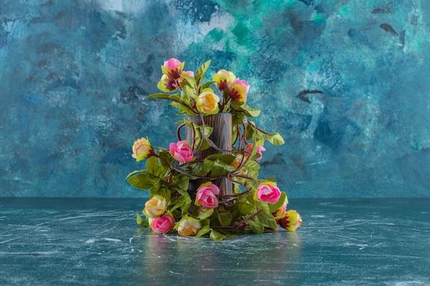 Flores coloridas em uma jarra de madeira, sobre o fundo azul.