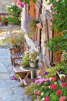 Flores coloridas em vasos e cadeiras em frente à fachada de uma casa rural