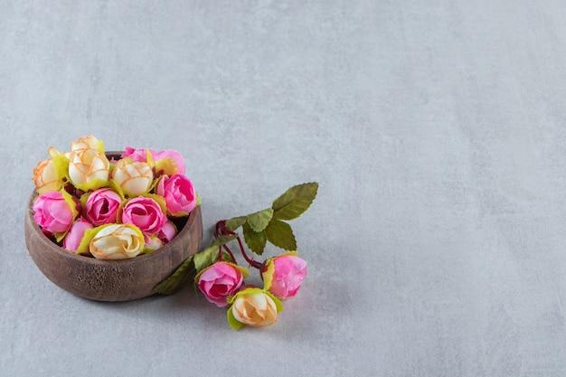Flores coloridas graciosas em uma tigela, na mesa branca.
