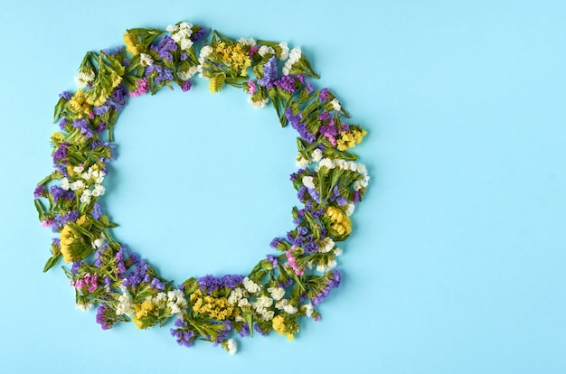 Flores coloridas na superfície azul, forma de círculo. lay plana