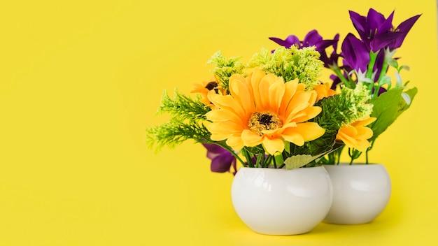 Flores coloridas no vaso pequeno branco contra fundo amarelo