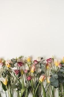Flores coloridas: tulipas, eucaliptos, rosas em branco