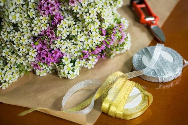 Flores com fitas na bancada de madeira da floricultura