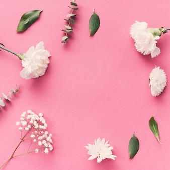 Flores com folhas espalhadas na mesa