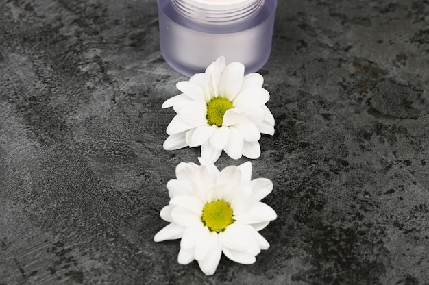 Flores com um pote de creme em um fundo escuro de mármore. vista de cima. cosmético natural.