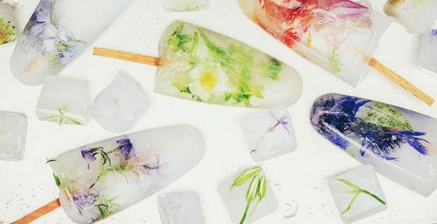 Flores congeladas em cubos de gelo e sorvete em uma vara. foco seletivo.
