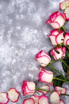 Flores cor-de-rosa bonitas na tabela de pedra cinzenta. borda floral.