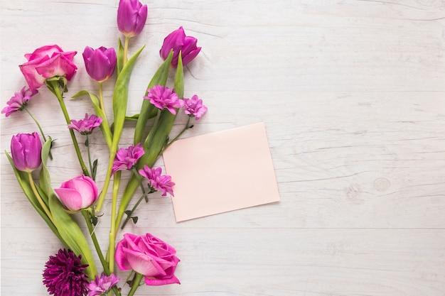 Flores cor de rosa com papel em branco na mesa de madeira