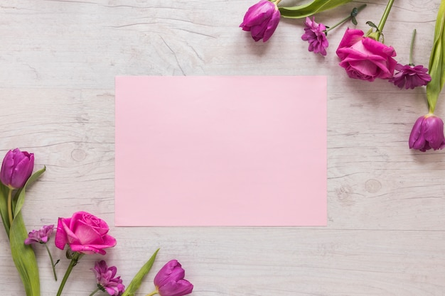 Flores cor de rosa com papel na mesa de madeira