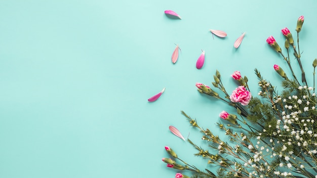 Flores cor de rosa com ramos de plantas na mesa