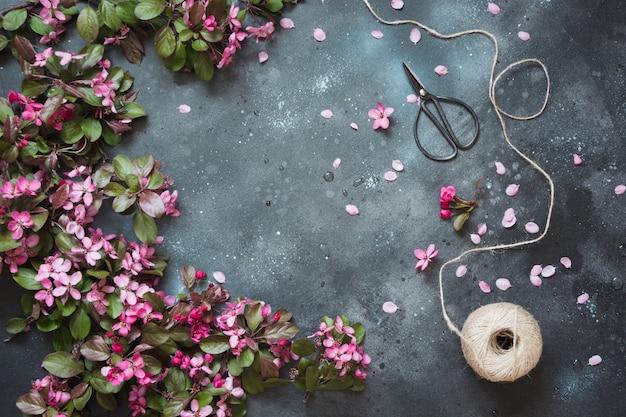 Flores cor-de-rosa da árvore de fruto de florescência com os acessórios para o floristics na tabela do vintage. .