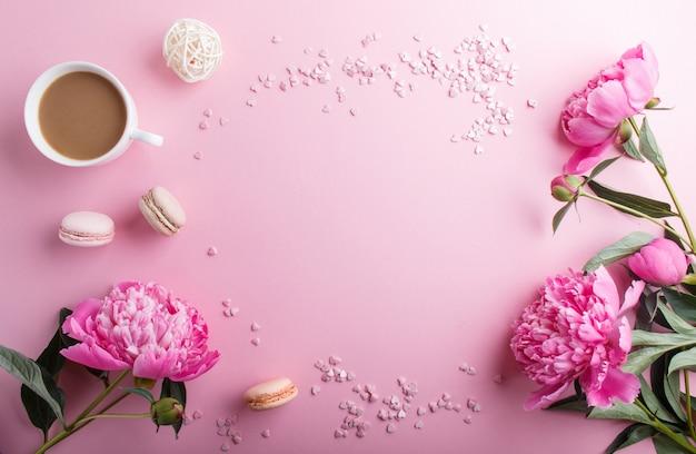 Flores cor-de-rosa da peônia e uma xícara de café no rosa pastel.