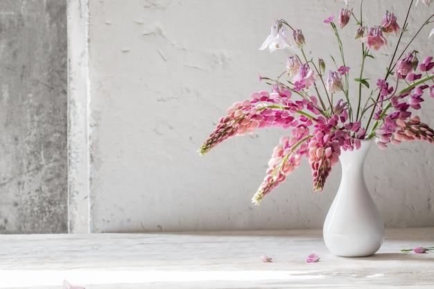 Flores cor de rosa de verão em um vaso branco sobre fundo branco antigo