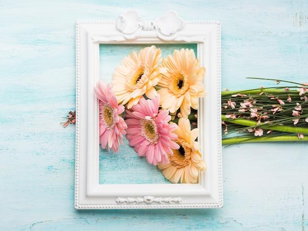 Flores cor-de-rosa e amarelas bonitas no frame branco no fundo verde pastel. mulher, cartão de dia da mãe.