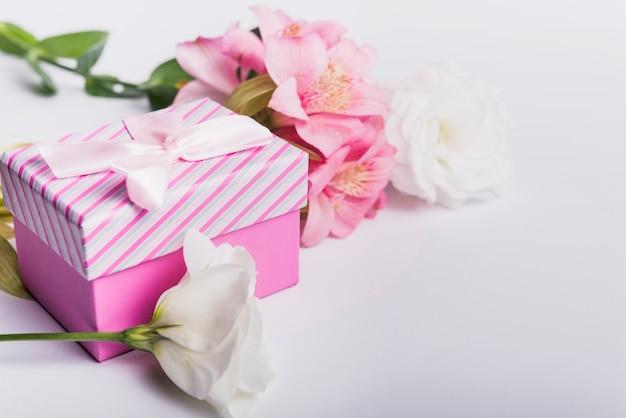 Flores cor de rosa e brancas com caixa de presente em pano de fundo branco